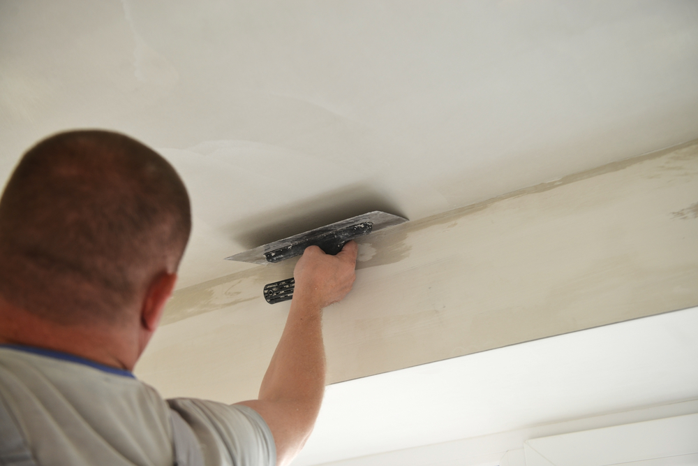 Man removing stippled ceiling